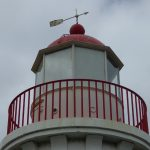 Red nose and weather vane on top of Lady Bay Upper Lighthouse